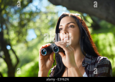 Mid adult woman with binoculars birdwatching in forest - Stock Photo