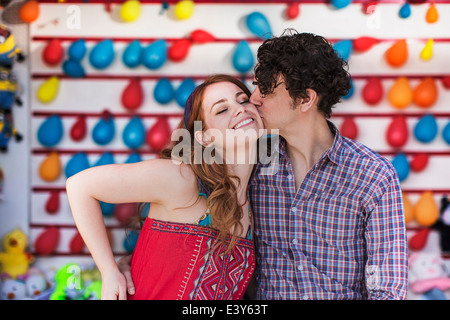 Romantic couple kissing on cheek at fairground stall - Stock Photo