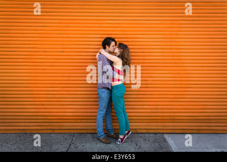 Romantic couple kissing in front of orange shutter - Stock Photo