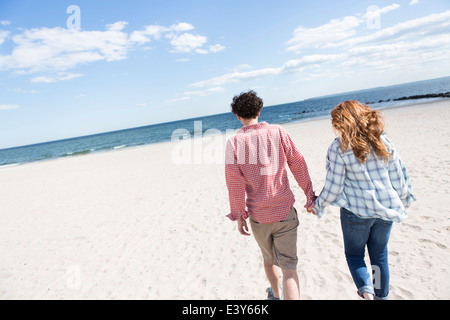 Romantic couple strolling hand in hand on beach - Stock Photo