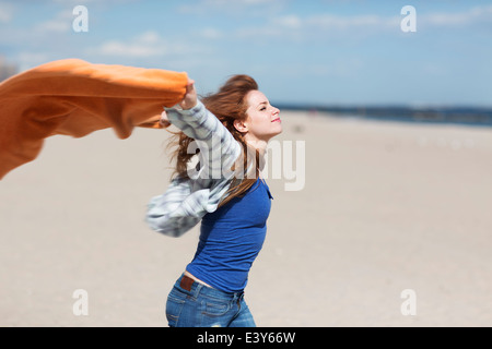 Young woman holding up blanket on windy beach - Stock Photo