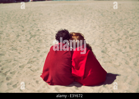 Rear view of romantic couple wrapped in blankets on beach - Stock Photo