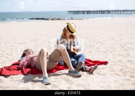 Couple sunbathing and playing ukulele on beach - Stock Photo