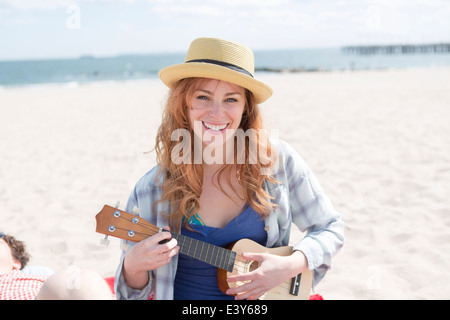 Portrait of young woman on beach playing ukelele - Stock Photo