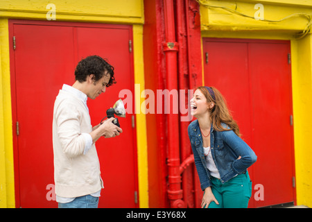 Couple having a laugh whilst taking photograph - Stock Photo