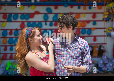 Couple with darts at fairground stall - Stock Photo