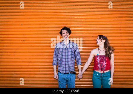 Portrait of couple in front of orange shutter - Stock Photo