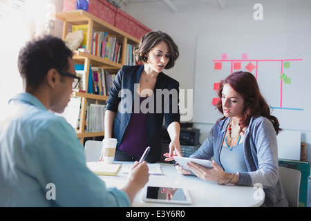 Young woman leading small meeting - Stock Photo