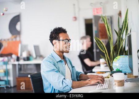 Young man working at computer in office - Stock Photo