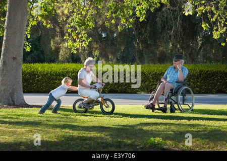 Three year old boy pushing grandmother on cycle with grandfather watching from wheelchair - Stock Photo