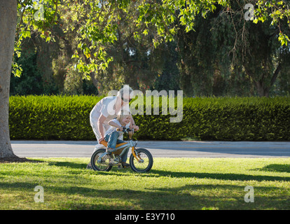 Three year old boy learning to cycle with grandmother in park - Stock Photo