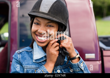 Horse rider putting on riding hat - Stock Photo
