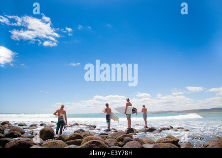 Four young male surfer friends watching sea - Stock Photo