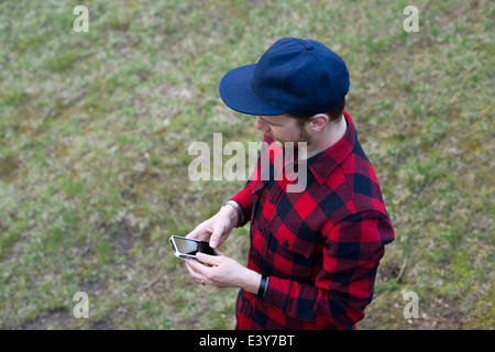 High angle view of mid adult man texting on smartphone - Stock Photo