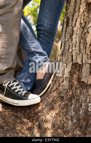 Legs and feet of young couple standing on tree - Stock Photo