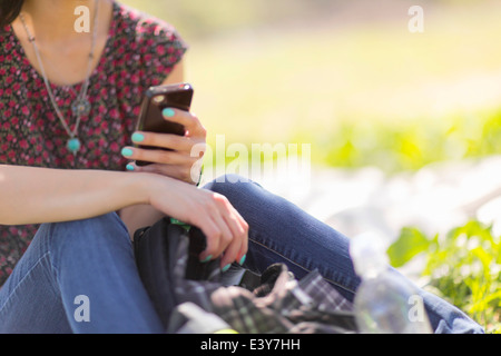 Cropped shot of young woman sitting in park with smartphone - Stock Photo