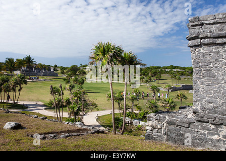 Tourist groups walk around the grounds at the Tulum archaeological site in Quintana Roo, Mexico. - Stock Photo