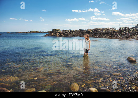 Young woman in the sea at the rocky coastal beach in Biddeford, Maine, USA - Stock Photo