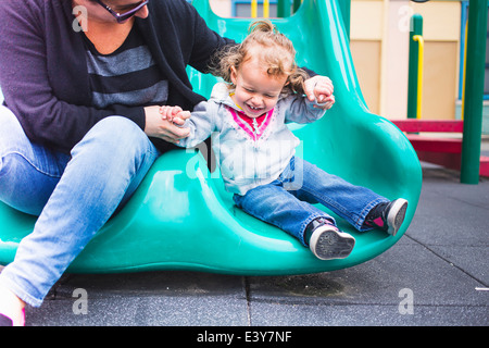 Mother and daughter going down slide in playground - Stock Photo