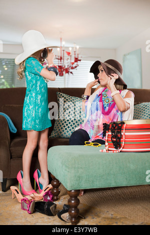 Mother and daughter dressing up in hats and high heels - Stock Photo