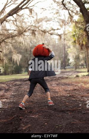 Boy running in forest holding onto pumpkin head - Stock Photo