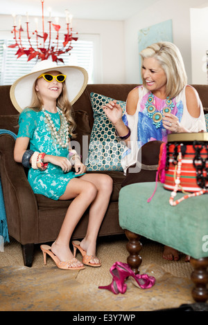 Mother dressing up daughter in hat and high heels - Stock Photo