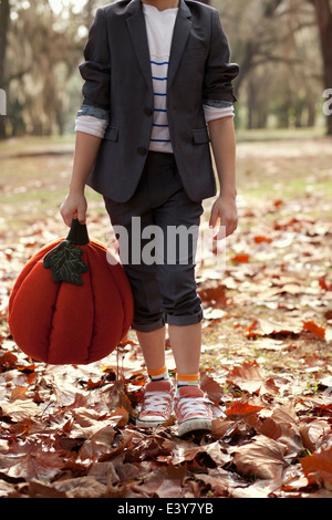 Cropped image of boy in forest holding pumpkin head - Stock Photo