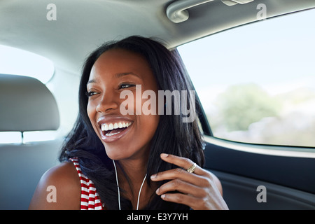 Young woman laughing car backseat - Stock Photo