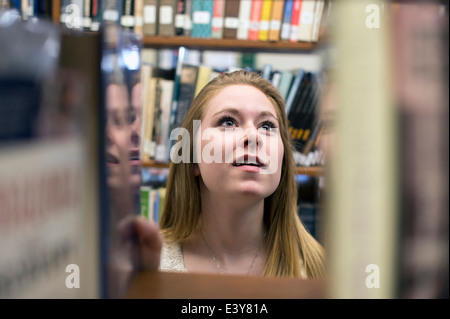 Young woman choosing book in library - Stock Photo