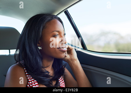 Portrait of young woman gazing through car backseat window - Stock Photo