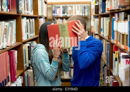 Young couple hiding behind book - Stock Photo