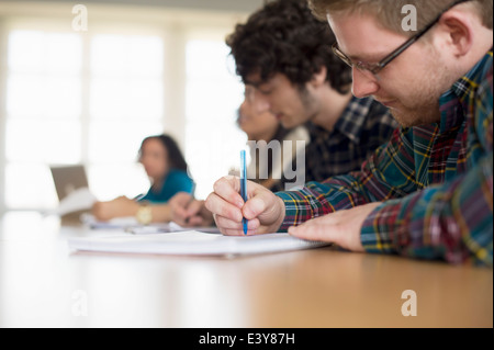 Students writing in classroom - Stock Photo