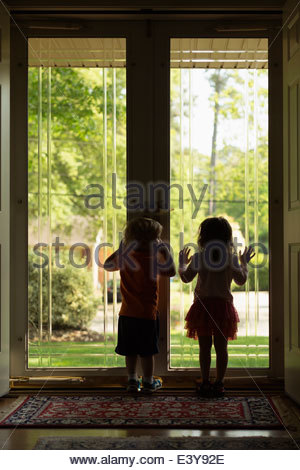 Male and female toddler friends silhouetted by patio door - Stock Photo
