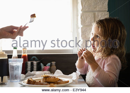 Hand of mother feeding toddler daughter in diner - Stock Photo