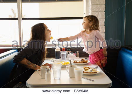 Toddler daughter feeding mother in diner - Stock Photo