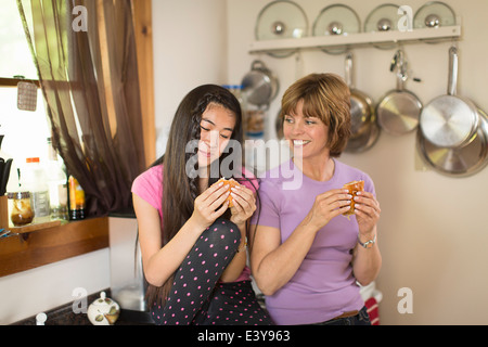Mid adult woman and teenage girl in kitchen, eating snack - Stock Photo
