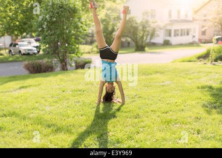 Teenage girl doing headstand - Stock Photo