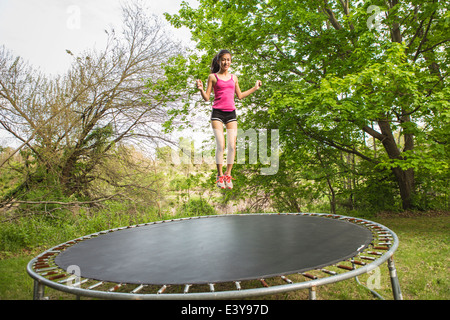 Teenage girl jumping on trampoline, outdoors - Stock Photo
