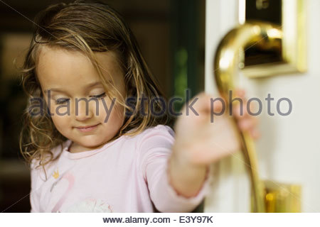 Female toddler opening door - Stock Photo