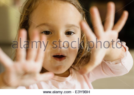 Close up of female toddler holding up hands - Stock Photo
