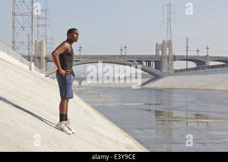 Young male runner taking a break on city riverbank - Stock Photo
