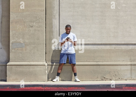 Young male runner texting on smartphone - Stock Photo