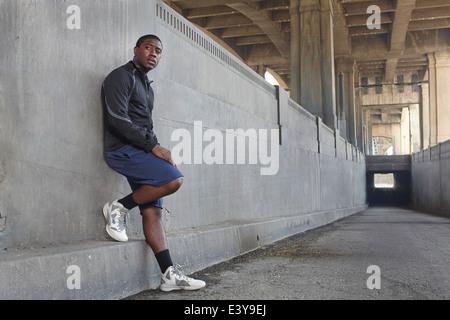 Young male runner taking a break on city bridge - Stock Photo