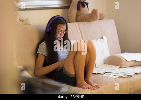 Teenage girl sitting on sofa, wearing headphones - Stock Photo