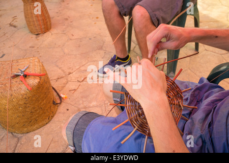 Skilled hands weaving wickerwork in the first steps of making a basket - Stock Photo