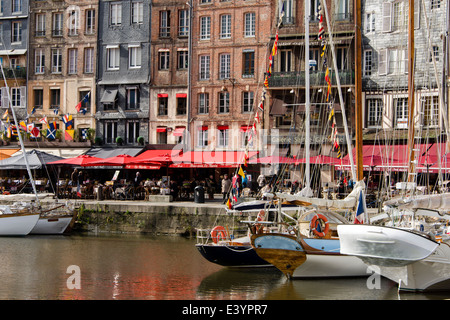 Sailboats docked along Vieux Bassin in front of bars and cafes along Quai Ste. Catherine, Honfleur, Normandy, France - Stock Photo