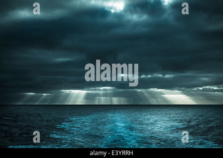 Sun rays shining through early morning cloud over Atlantic Ocean. View from deck of ship - Stock Photo