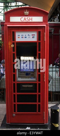 An old red telephone box converted to an ATM machine - Stock Photo