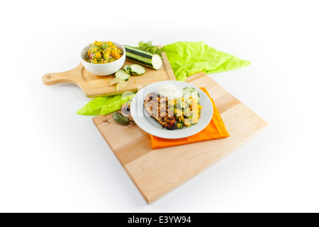 Layout of chicken meal on cutting boards. Sliced cucumber, mangos, and salad bowl. Optional cut out. - Stock Photo