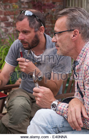 Two men in a garden puffing on electronic pipes, known as 'Vaping' whilst concentrating  on a laptop which is out - Stock Photo